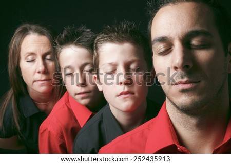 family portrait of four siblings in front of black background - stock photo