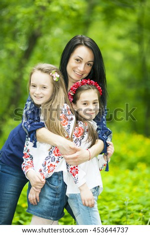 Family portrait of happy girls and mother in the park on a background of green trees - stock photo