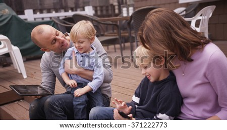 Family portrait of loving parents sharing handheld devices with children. - stock photo