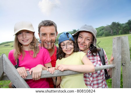Family portrait standing by a fence - stock photo