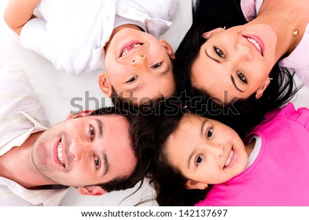 Family portrait with heads together lying on the floor - stock photo