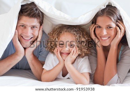 Family posing under a duvet while looking at the camera - stock photo