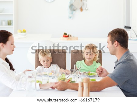 Family praying together before eating their salad for lunch in the kitchen - stock photo