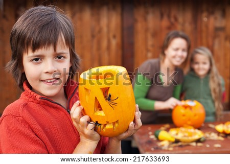 Family preparing for Halloween - boy showing his carved pumpkin jack o lantern - stock photo