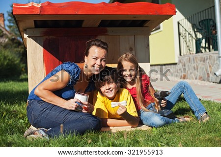 Family preparing the doghouse waiting happily for the new family member - a puppy dog - stock photo