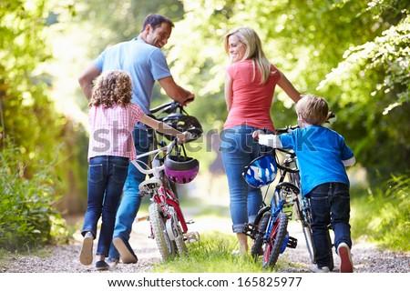 Family Pushing Bikes Along Country Track - stock photo
