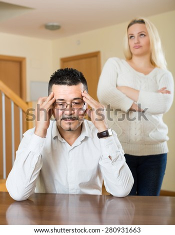 Family quarrel. Sad guy and angry young woman during quarrel in living room at home  - stock photo