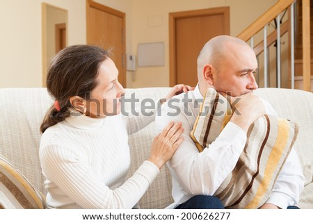 Family quarrel. Sad guy and woman during conflict in living room at home  - stock photo
