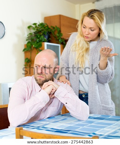 Family quarrel. Sad man and girl during quarrel  in living room at home  couple having problems at home. Focus on man - stock photo