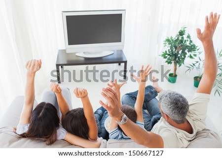 Family raising their arms in front of television at home - stock photo