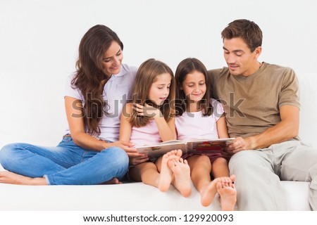 Family reading a story on a sofa in the living room - stock photo