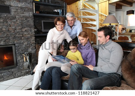 Family reading book on a sofa - stock photo
