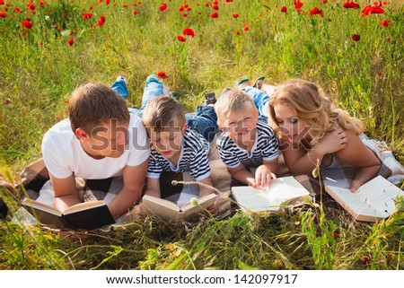 Family reading books laying on the grass - stock photo