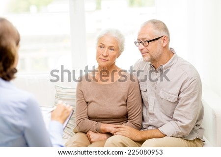 family, relations, age and people concept - senior couple and psychologist or social worker at home - stock photo