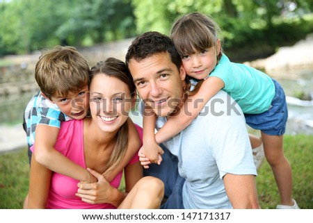 Family relaxing by river in countryside - stock photo