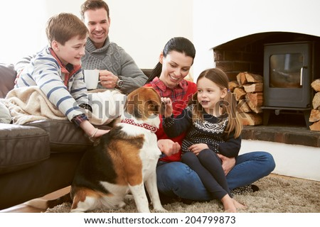 Family Relaxing Indoors And Stroking Pet Dog - stock photo