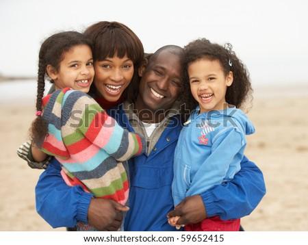 Family Relaxing On Winter Beach Break - stock photo