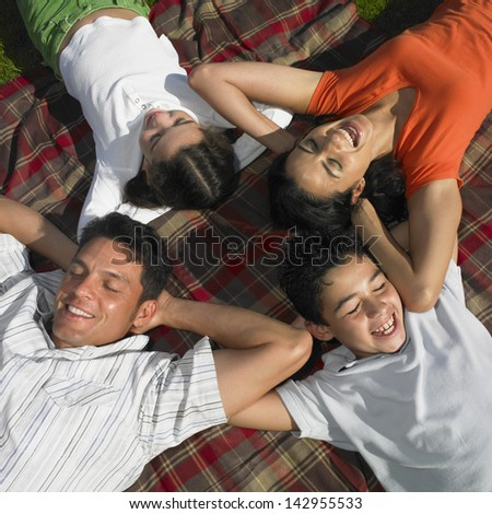 Family relaxing together on blanket - stock photo