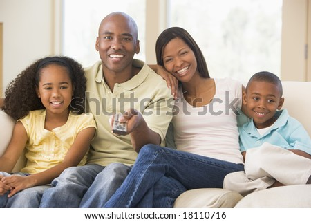 family relaxing watching television at home - stock photo