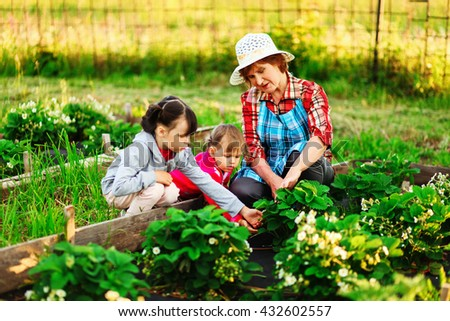 Family resting in garden and works in the beds. - stock photo