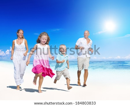 Family Running On a Beach Young family enjoying their summer vacation. - stock photo
