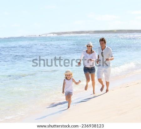 Family running on a white sandy beach - stock photo