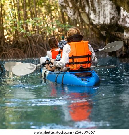 family sailing kayaking among the rocks by the sea - stock photo