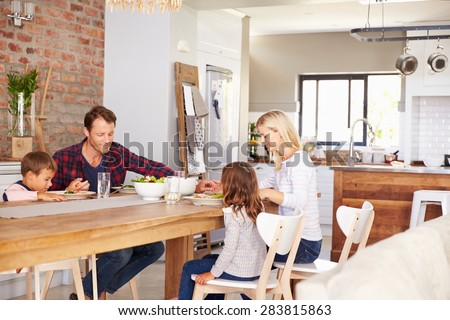 Family saying grace before dinner - stock photo