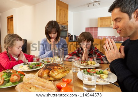 Family Saying Grace Before Eating Lunch Together In Kitchen - stock photo