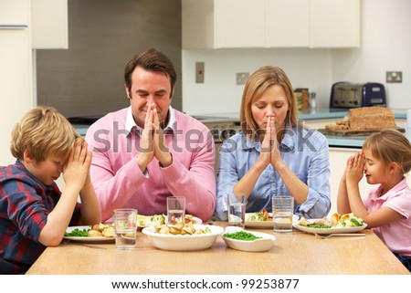 Family saying grace before meal - stock photo