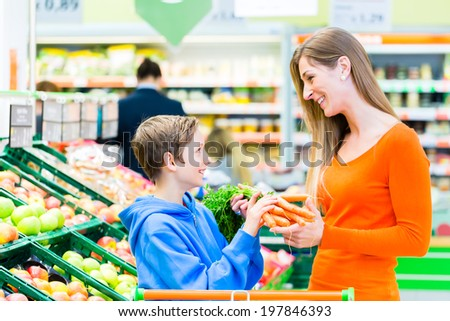 Family selecting fruits and vegetables while grocery shopping in supermarket  - stock photo