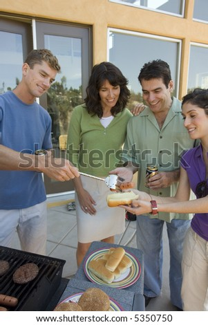 Family serving hot dogs off the grill - stock photo