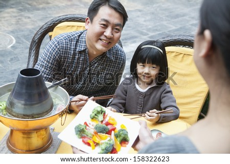 Family sharing and eating Chinese food  - stock photo