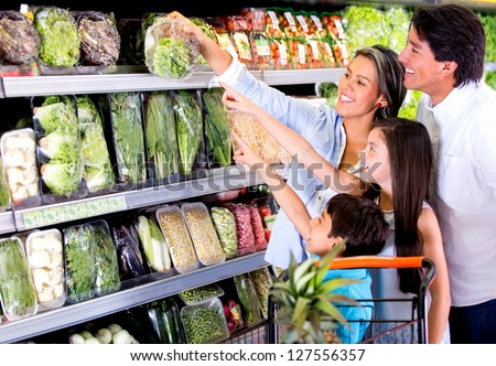 Family shopping at the supermarket and kids helping out - stock photo