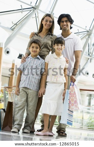 Family shopping in mall carrying bags - stock photo