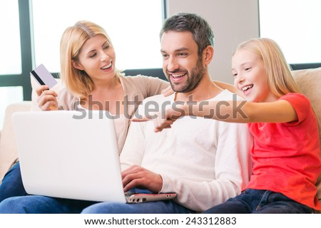 Family shopping online. Happy family of three bonding to each other and smiling while sitting on the couch and shopping online together  - stock photo