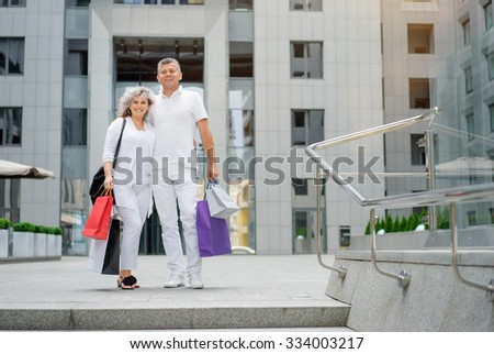 Family shopping. Outdoor portrait of Attractive elderly family couple holding bags. - stock photo