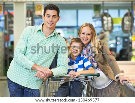 Family shopping. Young man and woman with child during shopping at supermarket store - stock photo