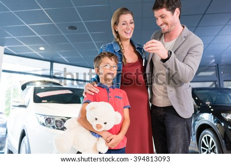 Family showing key to newly bought car in showroom of auto dealership - stock photo