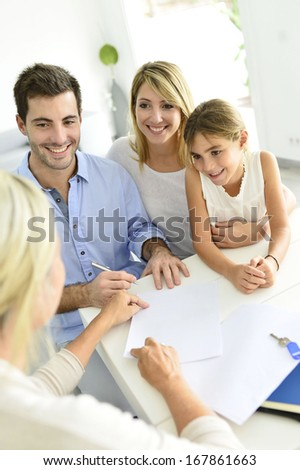 Family signing contract with home seller - stock photo