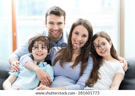 Family sitting on couch - stock photo