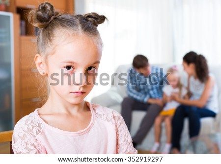 Family sitting on sofa and jealous sister standing apart - stock photo