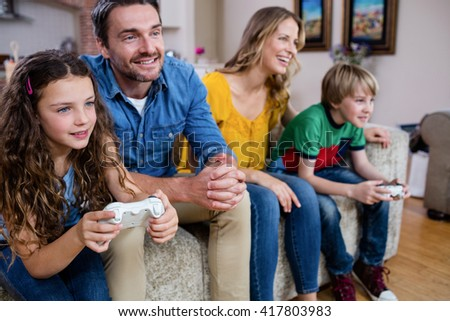 Family sitting on sofa and playing video game at home - stock photo