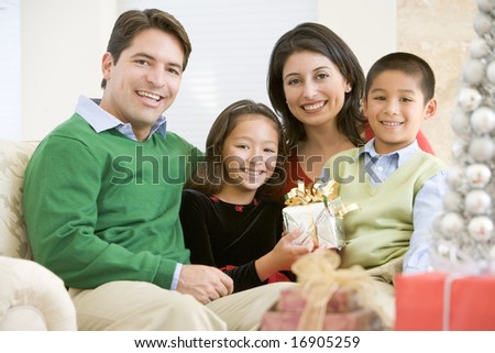 Family Sitting On Sofa Together,Holding A Christmas Gift - stock photo