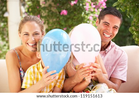 Family Sitting On Sofa Together With Balloons - stock photo