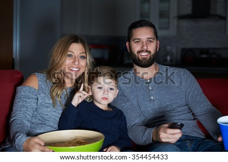 Family Sitting On Sofa Watching Television Together - stock photo