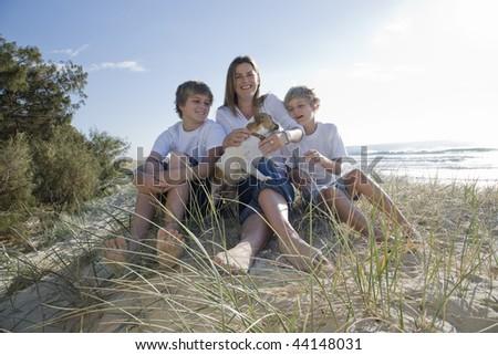 Family sitting on the beach - stock photo