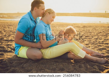 family sitting on the beach at sunrise - stock photo