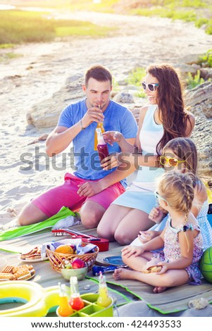Family sitting on the sand at the beach at the summer picnic. Green bucket with lemonade - stock photo