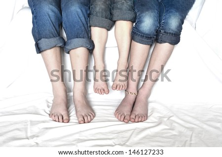 Family sitting with jeans rolled up sharing fun moment of happiness together bare feet - stock photo